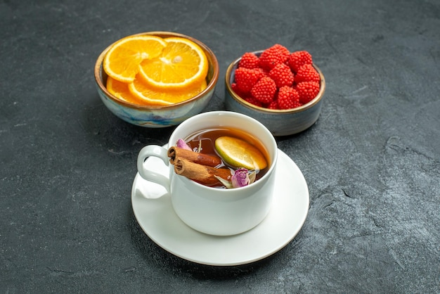 Front view cup of tea with orange slices and confitures on dark surface fruit citrus tea
