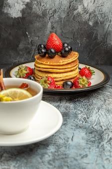 Vista frontale tazza di tè con frittelle e frutta su un cibo per la colazione al mattino piano scuro