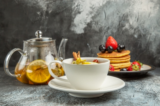Front view cup of tea with pancakes and fruits on a dark surface morning breakfast food