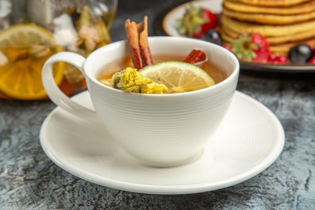 Vista frontale tazza di tè con frittelle e frutta sul cibo per la colazione del mattino superficie scura