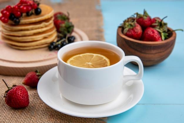 Vista frontale della tazza di tè con una fetta di limone e frittelle con ribes rosso e nero e fragole su una superficie blu