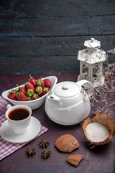 Front view cup of tea with strawberries on the dark surface tea drink fruit color