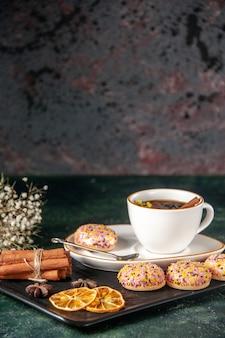 Vista frontale tazza di tè con biscotti dolci nel piatto e vassoio sulla superficie scura cerimonia di vetro dolce colazione colore zucchero torta dessert