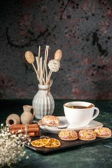 Vista frontale tazza di tè con biscotti dolci nel piatto e vassoio sulla superficie scura cerimonia di vetro dolce colazione zucchero torta dessert