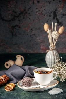 Vista frontale tazza di tè con biscotti al cioccolato dolce nel piatto e vassoio sulla superficie scura cerimonia di vetro prima colazione torta di zucchero dessert colore dolce