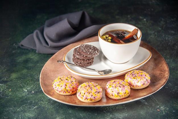 Vista frontale tazza di tè con biscotti al cioccolato dolce nel piatto e vassoio sulla superficie scura cerimonia di vetro dolce colazione torta dessert colore