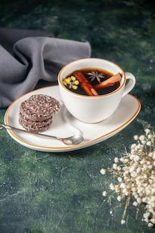 Vista frontale tazza di tè con biscotti al cioccolato dolce nel piatto e vassoio sulla superficie scura cerimonia di vetro dolce colazione zucchero colore della torta