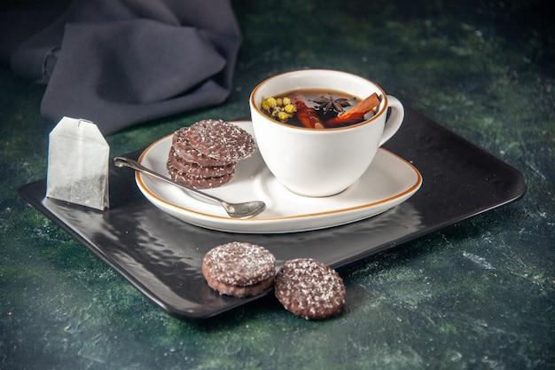 Vista frontale tazza di tè con biscotti al cioccolato dolce nel piatto e vassoio sulla superficie scura cerimonia di vetro dolce colazione zucchero torta dessert colore