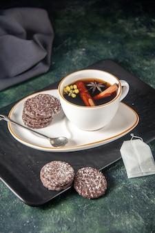 Vista frontale tazza di tè con biscotti al cioccolato dolce nel piatto e vassoio sulla superficie scura cerimonia di vetro dolce torta di zucchero colore del dessert