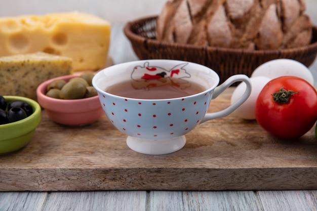 Vista frontale tazza di tè con pomodoro, uova di gallina e olive su un supporto