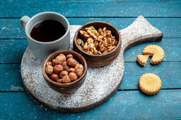 Front view cup of tea with walnuts and hazelnuts on blue rustic desk nut snack tea color
