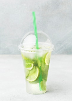 Front view of cup with soft drink and lime