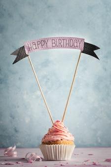 Vista frontale del cupcake con glassa e auguri di buon compleanno