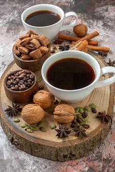 Vista frontale tazze di caffè con cannella e noci su zucchero chiaro biscotto color tè cacao dolce