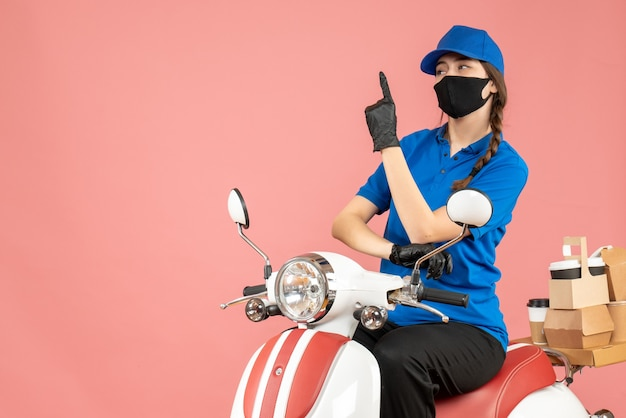 Front view of curious courier girl wearing medical mask and gloves sitting on scooter delivering orders pointing up on pastel peach background