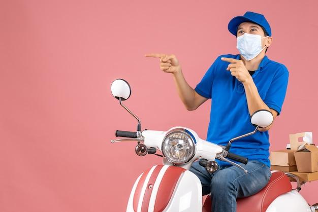 Vista frontale di un curioso corriere in maschera medica che indossa un cappello seduto su uno scooter che consegna ordini su sfondo color pesca pastello