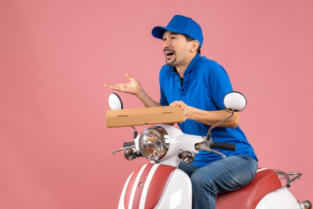 Front view of curious courier man wearing hat sitting on scooter holding order on pastel peach background