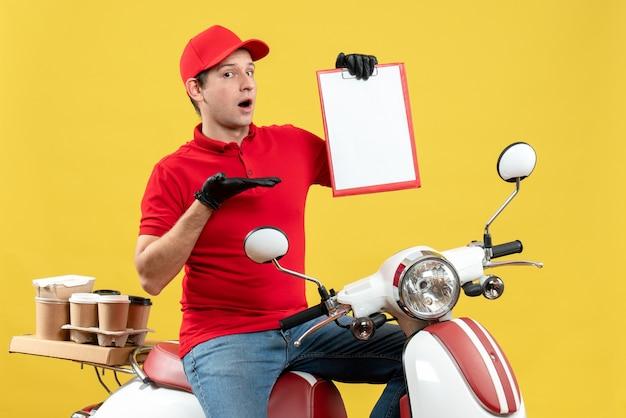 Vista frontale dell'uomo curioso del corriere che indossa guanti rossi della camicetta e del cappello nella mascherina medica che trasporta l'ordine che si siede sul documento della tenuta dello scooter
