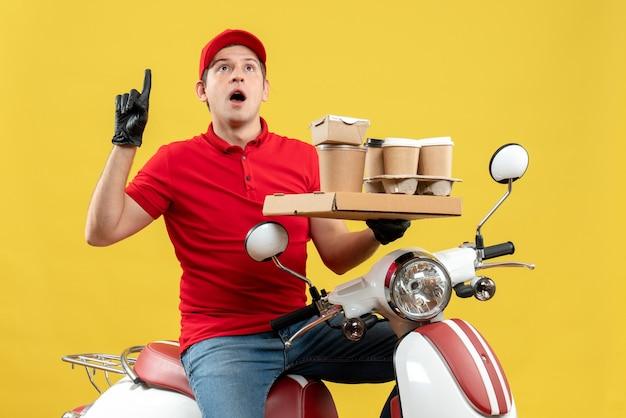 Vista frontale dell'uomo curioso del corriere che indossa guanti rossi della camicetta e del cappello nella mascherina medica che trasporta l'ordine che si siede sugli ordini della tenuta dello scooter che indicano verso l'alto