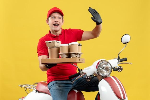 Vista frontale dell'uomo curioso del corriere che indossa guanti rossi della camicetta e del cappello nella mascherina medica che trasporta l'ordine che si siede sugli ordini della tenuta dello scooter