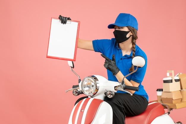 Vista frontale di una curiosa donna corriere che indossa maschera medica e guanti seduta su uno scooter con in mano fogli di carta vuoti che consegnano ordini su sfondo pesca pastello
