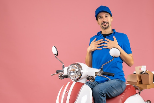 Front view of curious delivery guy wearing hat sitting on scooter pointing himself on pastel peach background