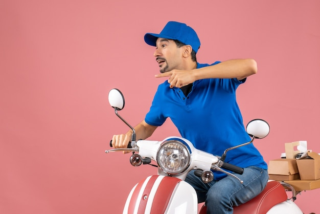 Front view of curious delivery guy wearing hat sitting on scooter and pointing something on the right side on pastel peach background