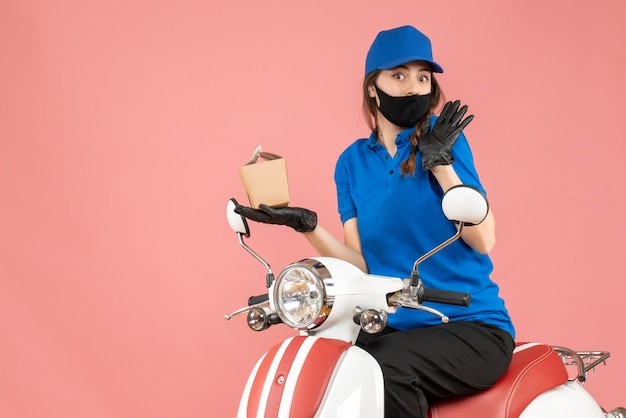 Front view of curious delivery person wearing medical mask and gloves sitting on scooter delivering orders on pastel peach background