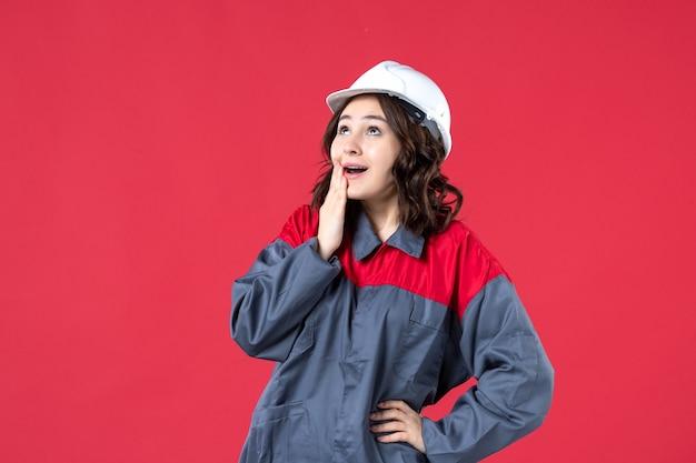 Vista frontale del curioso costruttore femminile in uniforme con elmetto e alzando lo sguardo su sfondo rosso isolato