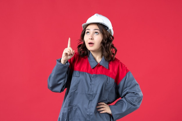 Front view of curious female builder in uniform with hard hat and pointing up on isolated red background