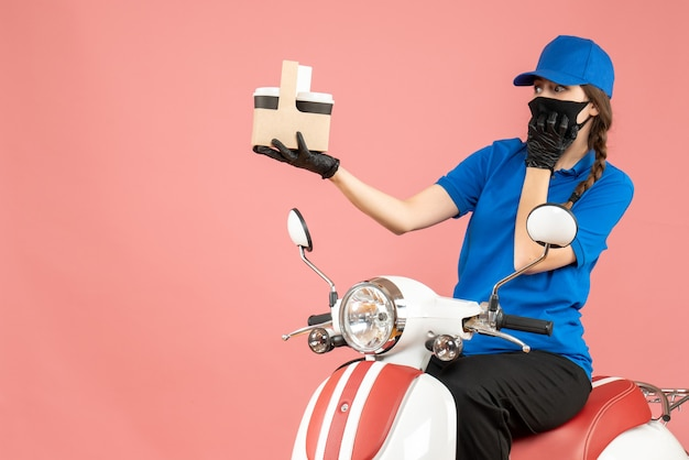 Front view of curious female delivery person wearing medical mask and gloves sitting on scooter delivering orders on pastel peach background