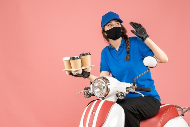 Vista frontale della curiosa donna delle consegne che indossa maschera medica e guanti seduti su uno scooter che tiene ordini su sfondo color pesca pastello pastel
