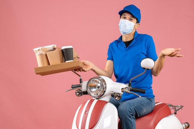 Front view of curious male delivery person in mask wearing hat sitting on scooter delivering orders on pastel peach background