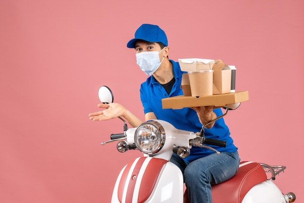 Front view of curious male delivery person in mask wearing hat sitting on scooter delivering orders on peach background