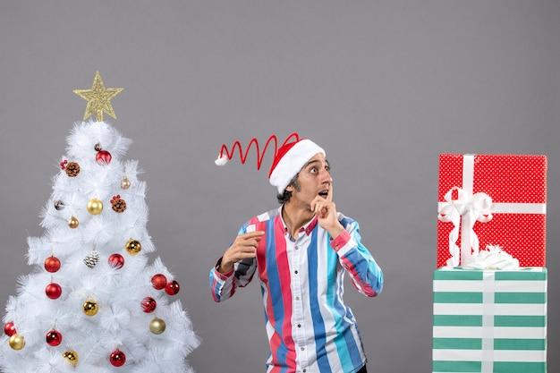 Вид спереди любопытный мужчина наблюдает за чем-то стоящим возле белой рождественской елки