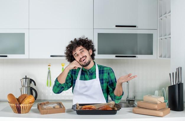 Vista frontale di un uomo curioso in piedi dietro il tavolo con sopra della pasta appena sfornata e che mi fa un gesto di chiamata nella cucina bianca