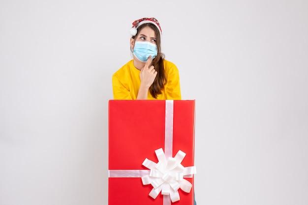 Вид спереди любопытная рождественская девушка в шляпе санта-клауса, стоящая за большим рождественским подарком
