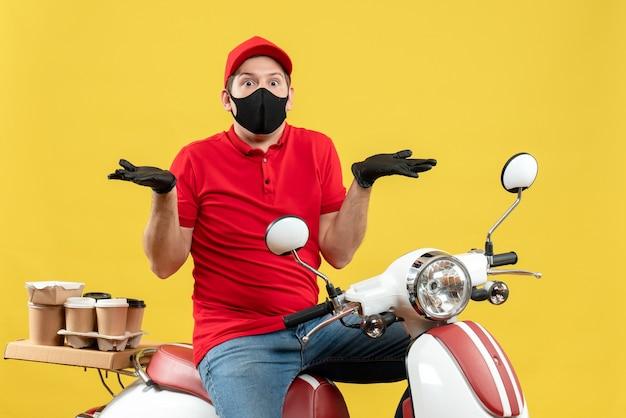 Vista frontale del giovane adulto curioso che indossa la camicetta rossa e guanti del cappello nella mascherina medica che trasporta l'ordine che si siede sullo scooter che indica entrambi i lati su fondo giallo