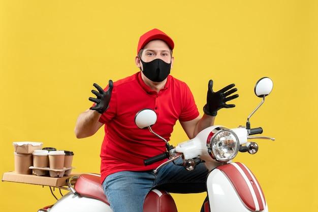 Vista frontale del giovane adulto curioso che indossa guanti rossi della camicetta e del cappello nella mascherina medica che trasporta l'ordine che si siede sul motorino su fondo giallo