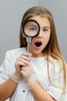 Vista frontale dello scienziato curioso della ragazza che per mezzo della lente d'ingrandimento