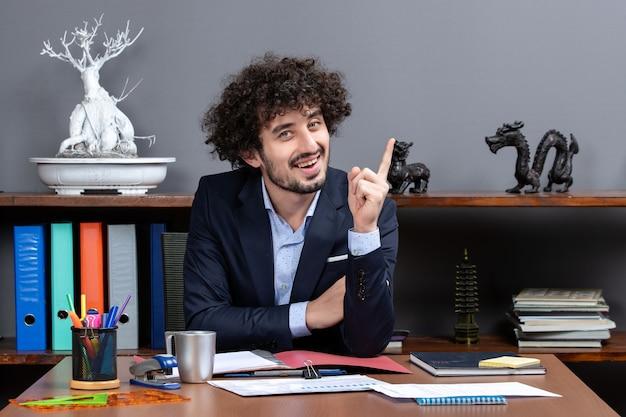 Вид спереди вьющиеся волосы бизнесмена, удивляющего своей идеей, сидя за столом в современном офисе