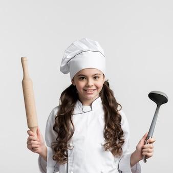 Вид спереди кудрявые волосы девушка держит инструменты для приготовления пищи
