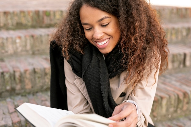 Front view curly woman reading outdoors