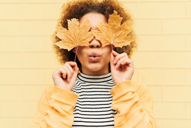葉で彼女の目を覆っている正面巻き毛の若い女性