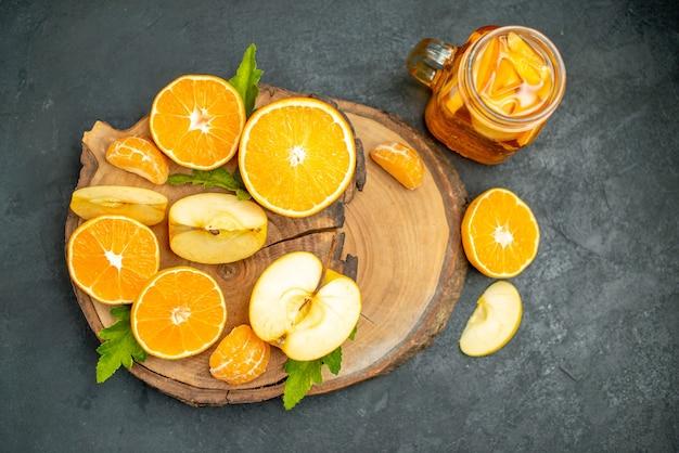 Вид спереди нарезанные яблоки и апельсины на коктейле из деревянной доски на темном фоне