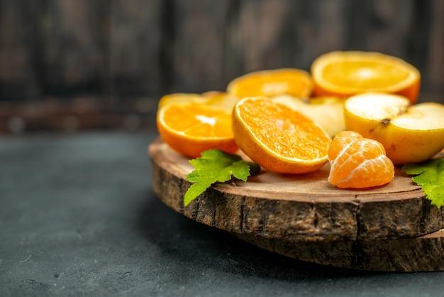 전면 보기는 어두운 배경에 있는 나무 판자에 사과와 오렌지를 잘라냅니다.