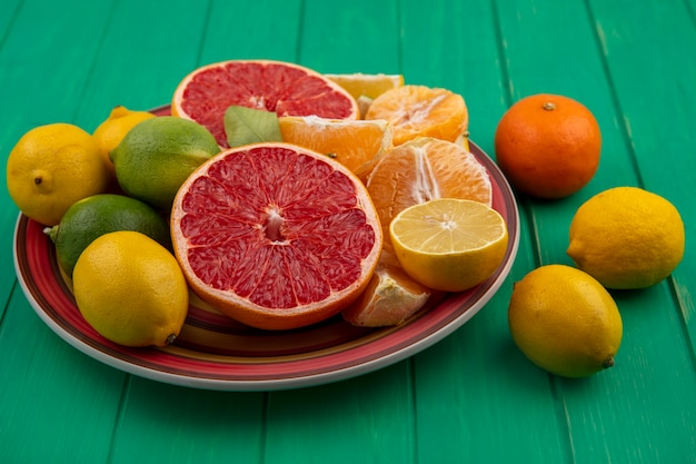 Вид спереди разрезанный пополам грейпфрут с очищенными апельсинами и лимоном с лаймом на тарелке на зеленом фоне