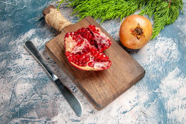 Vista frontale di un melograno tagliato sul tagliere di un coltello da pranzo al melograno su sfondo blu-bianco