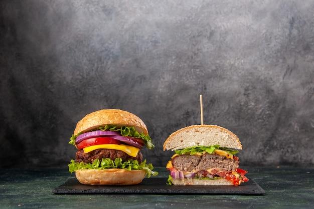 Vista frontale di interi gustosi panini tagliati su vassoio nero su superficie di colore misto scuro