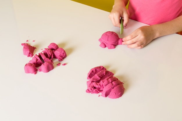 A front view cute adorable boy in pink t-shirt playing with colorful kinetic sand